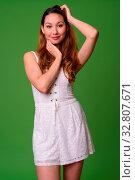 Купить «Studio shot of young beautiful Asian woman against green background», фото № 32807671, снято 27 мая 2020 г. (c) easy Fotostock / Фотобанк Лори