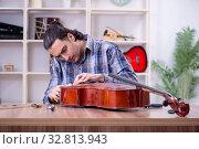 Купить «Young handsome repairman repairing cello», фото № 32813943, снято 4 апреля 2019 г. (c) Elnur / Фотобанк Лори