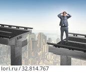 Купить «Young businessman in uncertainty concept with bridge», фото № 32814767, снято 27 января 2020 г. (c) Elnur / Фотобанк Лори