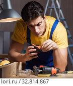 Купить «The worker working in repair workshop in woodworking concept», фото № 32814867, снято 11 августа 2017 г. (c) Elnur / Фотобанк Лори