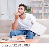 Купить «Man eating pizza having a takeaway at home relaxing resting», фото № 32815083, снято 18 июля 2017 г. (c) Elnur / Фотобанк Лори
