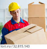 The young man working in relocation services with boxes. Стоковое фото, фотограф Elnur / Фотобанк Лори