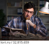 Купить «Archeologist working late night in office», фото № 32815659, снято 15 марта 2017 г. (c) Elnur / Фотобанк Лори