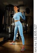 Купить «Young beautiful girl in a workout gear lifting weights», фото № 32835527, снято 11 декабря 2019 г. (c) Алексей Кузнецов / Фотобанк Лори