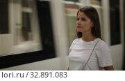Young woman waiting train in platform of underground station. Стоковое видео, видеограф Яков Филимонов / Фотобанк Лори