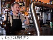 Купить «Adult barman is giving beer with foam to client», фото № 32891915, снято 18 сентября 2017 г. (c) Яков Филимонов / Фотобанк Лори