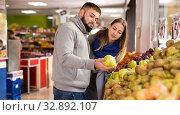 Купить «Friendly couple examining apples in grocery shop», фото № 32892107, снято 20 ноября 2019 г. (c) Яков Филимонов / Фотобанк Лори