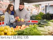 Купить «Friendly couple examining apples in grocery shop», фото № 32892135, снято 20 ноября 2019 г. (c) Яков Филимонов / Фотобанк Лори