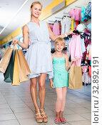 Купить «Female with packs and girl buying clothes in the dress shop», фото № 32892191, снято 27 июля 2017 г. (c) Яков Филимонов / Фотобанк Лори