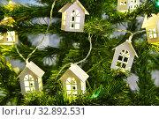 Купить «Светодиодная гирлянда из деревянных домиков на ёлке», эксклюзивное фото № 32892531, снято 20 января 2019 г. (c) Dmitry29 / Фотобанк Лори