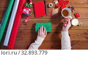 Купить «hands wrapping christmas gift and writing note», видеоролик № 32893779, снято 19 декабря 2019 г. (c) Syda Productions / Фотобанк Лори