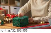 Купить «woman wrapping christmas gift into paper at home», видеоролик № 32893955, снято 18 декабря 2019 г. (c) Syda Productions / Фотобанк Лори