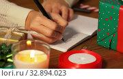 Купить «female's hands writing letter to santa in notebook», видеоролик № 32894023, снято 18 декабря 2019 г. (c) Syda Productions / Фотобанк Лори