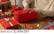Купить «woman wrapping christmas gift into paper at home», видеоролик № 32894091, снято 18 декабря 2019 г. (c) Syda Productions / Фотобанк Лори