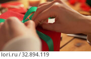 hands packing christmas gift and attaching tag. Стоковое видео, видеограф Syda Productions / Фотобанк Лори