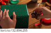 Купить «hands packing christmas gift and choosing bow», видеоролик № 32894255, снято 18 декабря 2019 г. (c) Syda Productions / Фотобанк Лори