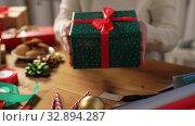 Купить «woman packing christmas gifts at home», видеоролик № 32894287, снято 18 декабря 2019 г. (c) Syda Productions / Фотобанк Лори