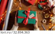 Купить «hands holding christmas gift with name tag», видеоролик № 32894363, снято 18 декабря 2019 г. (c) Syda Productions / Фотобанк Лори