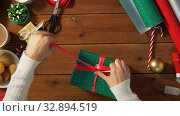 hands packing christmas gift and tying bow. Стоковое видео, видеограф Syda Productions / Фотобанк Лори