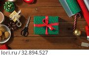 Купить «woman packing christmas gift at home», видеоролик № 32894527, снято 18 декабря 2019 г. (c) Syda Productions / Фотобанк Лори