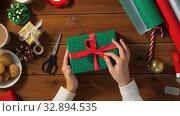 Купить «woman packing christmas gift at home», видеоролик № 32894535, снято 18 декабря 2019 г. (c) Syda Productions / Фотобанк Лори