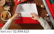 Купить «woman wrapping christmas gift into paper at home», видеоролик № 32894623, снято 18 декабря 2019 г. (c) Syda Productions / Фотобанк Лори
