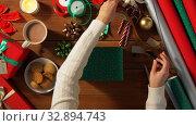 Купить «hands packing christmas gift and choosing bow», видеоролик № 32894743, снято 18 декабря 2019 г. (c) Syda Productions / Фотобанк Лори
