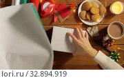woman wrapping camera for christmas gift. Стоковое видео, видеограф Syda Productions / Фотобанк Лори
