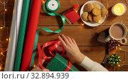 Купить «woman wrapping camera for christmas gift», видеоролик № 32894939, снято 18 декабря 2019 г. (c) Syda Productions / Фотобанк Лори