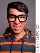 Studio shot of young Asian nerd man wearing hoodie and eyeglasses against gray background. Стоковое фото, фотограф Zoonar.com/Toni Rantala / easy Fotostock / Фотобанк Лори