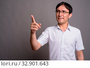 Studio shot of young Asian nerd man wearing eyeglasses against gray background. Стоковое фото, фотограф Zoonar.com/Toni Rantala / easy Fotostock / Фотобанк Лори