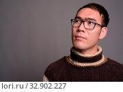 Studio shot of young Asian man wearing turtleneck sweater and eyeglasses against gray background. Стоковое фото, фотограф Zoonar.com/Toni Rantala / easy Fotostock / Фотобанк Лори