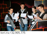 Group of laser tag players read a contract and game conditions. Стоковое фото, фотограф Яков Филимонов / Фотобанк Лори