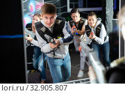 Купить «Portrait of happy young man with laser pistol and playing laser tag with his friends in dark room», фото № 32905807, снято 4 апреля 2020 г. (c) Яков Филимонов / Фотобанк Лори
