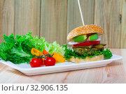 Купить «Vegetarian hamburger with soybean patty, fresh vegetables and avocado at plate», фото № 32906135, снято 28 января 2020 г. (c) Яков Филимонов / Фотобанк Лори