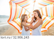 Купить «Mom with a small daughter walks along the beach with an umbrella on a sunny summer day.», фото № 32906243, снято 18 июля 2019 г. (c) Акиньшин Владимир / Фотобанк Лори
