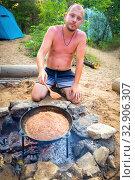 Купить «A young man cooks outdoors pilaf in a cauldron at the stake.», фото № 32906307, снято 19 июля 2019 г. (c) Акиньшин Владимир / Фотобанк Лори