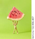 Купить «Fresh ripe peace of watermelon in the hands of wooden mannequin model.», фото № 32906407, снято 22 августа 2019 г. (c) Ярослав Данильченко / Фотобанк Лори