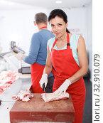 Купить «Two seller working in shop, woman cutting meat», фото № 32910079, снято 22 июня 2018 г. (c) Яков Филимонов / Фотобанк Лори