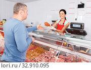 Купить «Smiling seller offering customer different sausages», фото № 32910095, снято 22 июня 2018 г. (c) Яков Филимонов / Фотобанк Лори