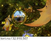 Купить «Изображение полумесяца с носом, ртом и глазами и блестящий шар, в котором отражается дом, украшают елку», фото № 32910507, снято 5 января 2020 г. (c) Наталья Николаева / Фотобанк Лори