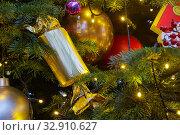 Купить «Большая хлопушка, шары и электрическая гирлянда с лампочками висят на новогодней елке», фото № 32910627, снято 5 января 2020 г. (c) Наталья Николаева / Фотобанк Лори