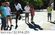 Купить «Happy smiling little friends playing with chinese jumping rope at playground», видеоролик № 32914251, снято 7 июня 2019 г. (c) Яков Филимонов / Фотобанк Лори
