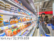 Russia Samara November 2019: An old woman near shelves with convenience foods in a store. Text in Russian: mussels herring. Редакционное фото, фотограф Акиньшин Владимир / Фотобанк Лори