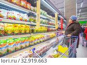 Russia Samara November 2019: An elderly woman near the shelves with mayonnaise. Russian text: Mayonnaise with lemon juice. Provencal Ryaba olive on a quail egg. Редакционное фото, фотограф Акиньшин Владимир / Фотобанк Лори
