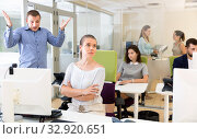 Upset girl sitting at laptop in coworking space while dissatisfied businessman pointing out mistakes in her work. Стоковое фото, фотограф Яков Филимонов / Фотобанк Лори