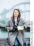 Купить «woman with luggage posing at quay and smiling», фото № 32921003, снято 27 марта 2017 г. (c) Яков Филимонов / Фотобанк Лори