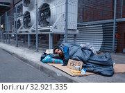 Купить «Dirty homeless with help sign lies on city street», фото № 32921335, снято 26 октября 2019 г. (c) Tryapitsyn Sergiy / Фотобанк Лори