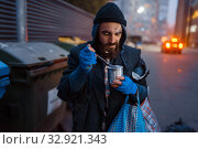 Homeless eating canned food on city street. Стоковое фото, фотограф Tryapitsyn Sergiy / Фотобанк Лори