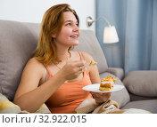 Купить «woman sitting on sofa with fresh cake», фото № 32922015, снято 25 февраля 2020 г. (c) Яков Филимонов / Фотобанк Лори